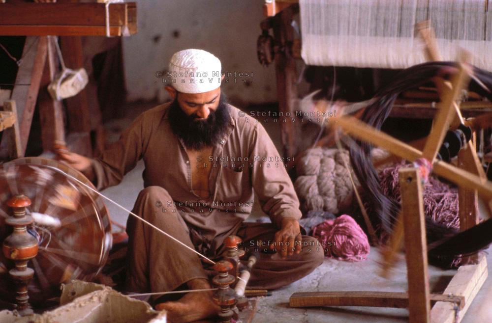 Pakistan Peshawar  1986.. Afghan works to the loom in Refugee Camp