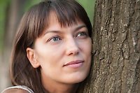Woman leans on tree trunk with a faraway look in her eyes