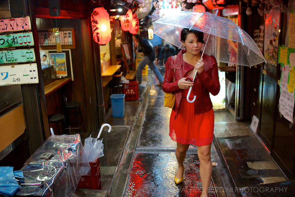 A girl walks by the narrow and once infamous 'Piss alley' on a rainy night. The passage is also a shortcut to get to the busy Shinjuku train station. Tokyo, Japan.