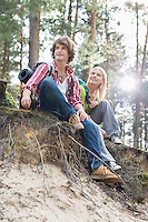 Full length of hiking couple sitting on edge of cliff in forest