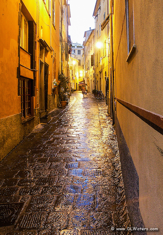 Narrow rainy street scene in Monterosso Italy.