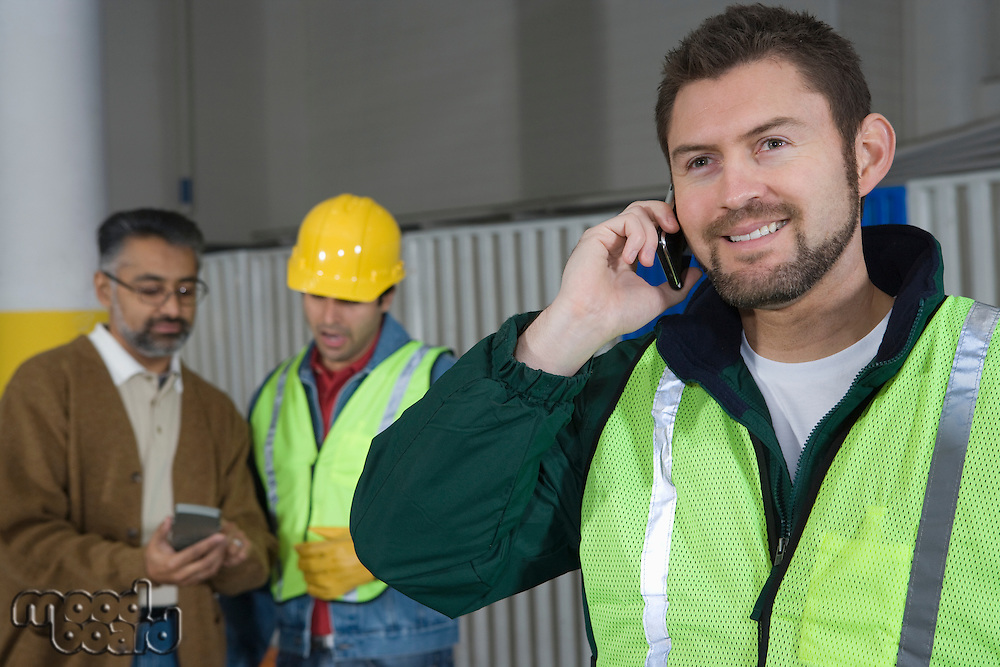 Man standing in factory using telephone colleagues in background