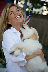 Woman holding a puppy laughing and getting licks on her face