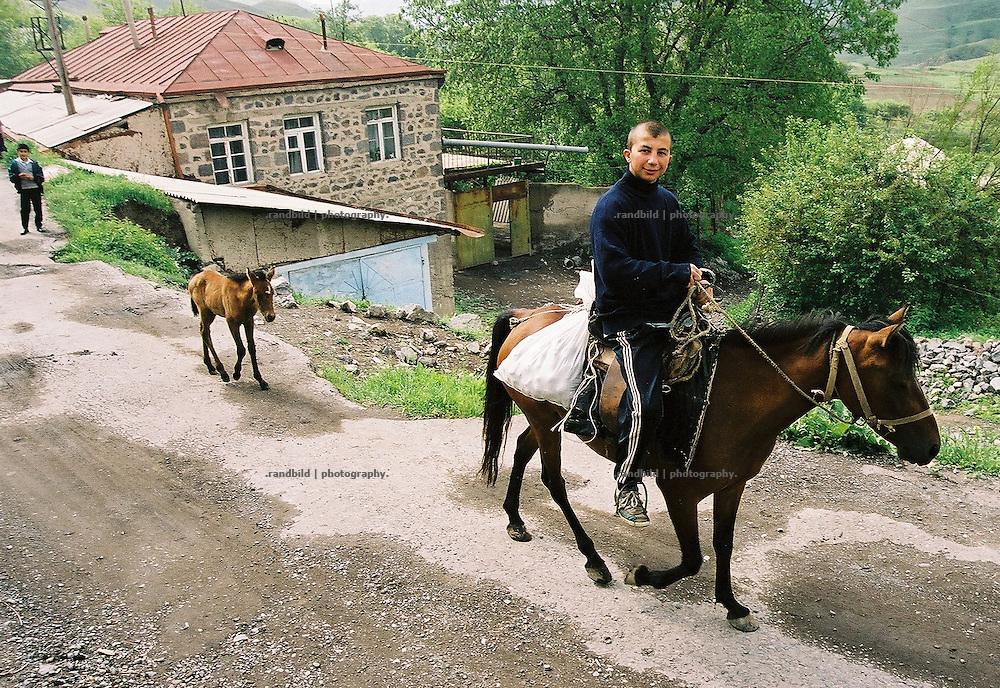 Ein junger Mann reitet mit seinem Pferd und dessen Fohlen durch ein armenisches Dorf in den Bergen um die Stadt Sissian. A boy rides a horse in rural armenian village.