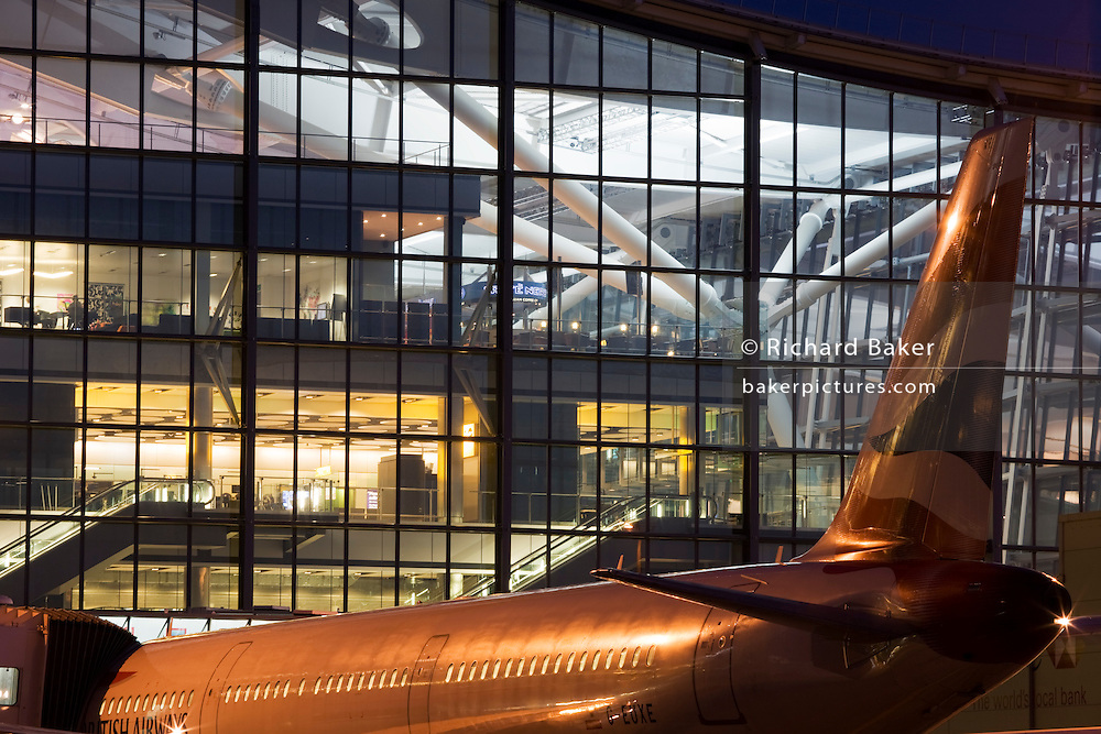 "An exterior view of Heathrow Airport's Terminal 5 building in West London. Created by the Richard Rogers Partnership (now Rogers Stirk Harbour and Partners). A British Airways airliner is parked at its Arrival/Departure gate in front of the bright lights that shine through huge window panes of glass. At a cost of £4.3 billion, the 400m long T5 is the largest free-standing building in the UK with the capacity to serve around 30 million passengers a year. The Terminal 5 public inquiry was the longest in UK history, lasting four years from 1995 to 1999. From writer Alain de Botton's book project ""A Week at the Airport: A Heathrow Diary"" (2009). ..."