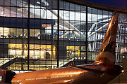 """An exterior view of Heathrow Airport's Terminal 5 building in West London. Created by the Richard Rogers Partnership (now Rogers Stirk Harbour and Partners). A British Airways airliner is parked at its Arrival/Departure gate in front of the bright lights that shine through huge window panes of glass. At a cost of £4.3 billion, the 400m long T5 is the largest free-standing building in the UK with the capacity to serve around 30 million passengers a year. The Terminal 5 public inquiry was the longest in UK history, lasting four years from 1995 to 1999. From writer Alain de Botton's book project """"A Week at the Airport: A Heathrow Diary"""" (2009). ..."""