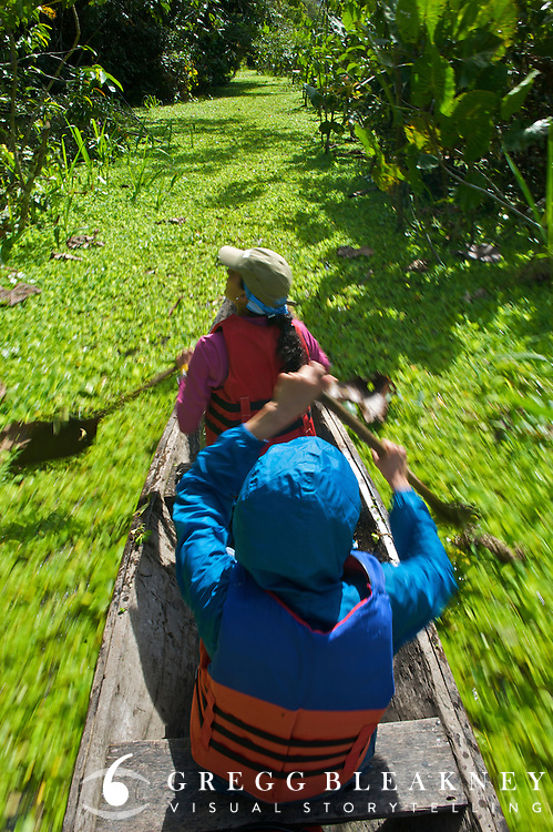 Travelers paddle through a green trail connecting Marasha Lake to the Amazon River - Amazonas - Peru