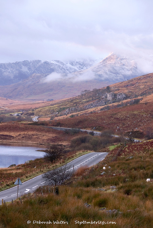 Snowdonia winter landscape as first rays of morning sunlight strike a snow covered mountain emerging from clouds, Capel Curig, Wales, UK
