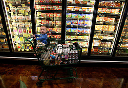 01 Feb 2006. Uptown, New Orleans, Louisiana.  Post Katrina. <br /> The Whole Foods supermarket reopens amidst great celebration 5 months after  the city was hit by Hurricane Katrina.  A young child sits in a shopping cart in the frozen food section.<br /> Photo; Charlie Varley/varleypix.com