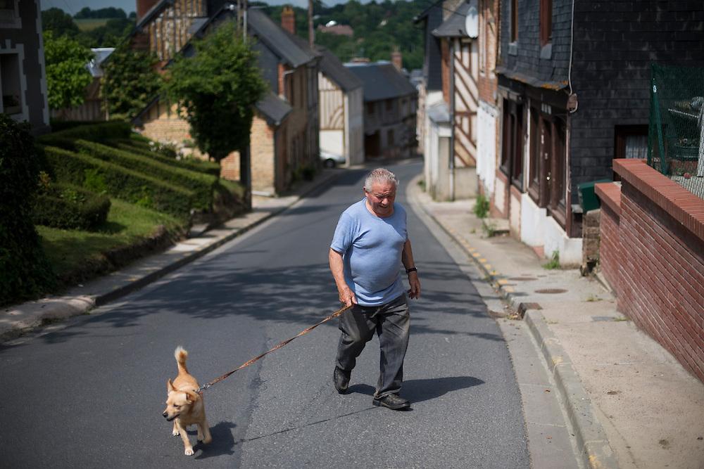 Un habitant prom&egrave;ne son chien &agrave; Cambremer, &quot;capitale du cidre&quot;.<br /> Cambremer, France. 27/06/2013.