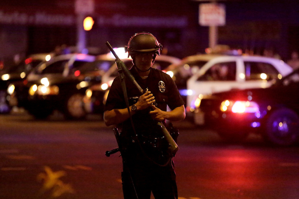 A Los Angeles Police officer stands watch as they try to remove protesters from the intersection of Exposition and Crenshaw boulevards, following the George Zimmerman verdict in Los Angeles, California, July 13, 2013. A Florida jury acquitted Zimmerman on Saturday for the shooting death of unarmed black teenager Trayvon Martin, setting free a man who had become a polarizing figure in the national debate over racial profiling and self-defense laws. REUTERS/Jason Redmond   (UNITED STATES - Tags: CRIME LAW CIVIL UNREST)