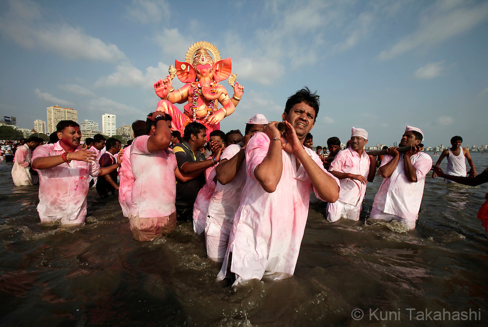 Men carry an Ganesha idol in ocean for immersion in Mumbai, India on Sep 22, 2010 on the last day of Ganpati festival. The 10-day hindu festival, celebrating the birthday of Lord Ganesha who is widely worshiped as the god of wisdom, prosperity and good fortune, attracts tens of thousands people..Photo by Kuni Takahashi