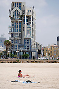 Israel, Tel Aviv, a woman sunbathing on the beach, a modern building on Trumpeldor street in the background