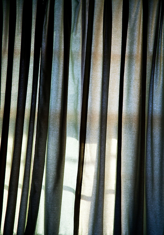 Sunlight hits a window curtain as seen from inside a motel room.