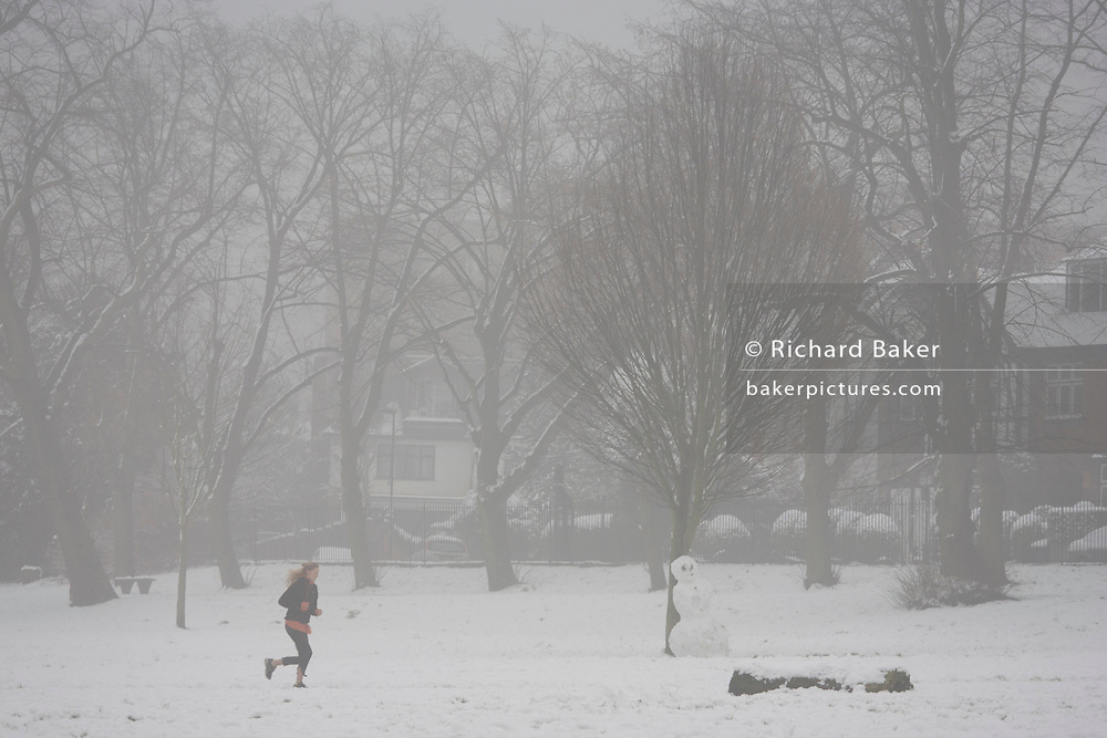 A lone lady jogger runs along the top of a hill in her local park. During a prolonged cold spell of bad weather, snow fell continuously on the capital days before, allowing families the chance to enjoy the bleak conditions in Ruskin Park in the borough of Lambeth.