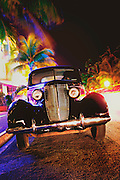 A 1937 Nash Lafayette coupe parked  in South Beach's historic, Art Deco District, on palm tree lined and neon-lit Ocean Drive in 2007.