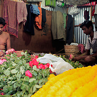 Asia, India, Calcutta. Scene from the flower market in Calcutta, where the men are stringing garlands of fresh flowers.