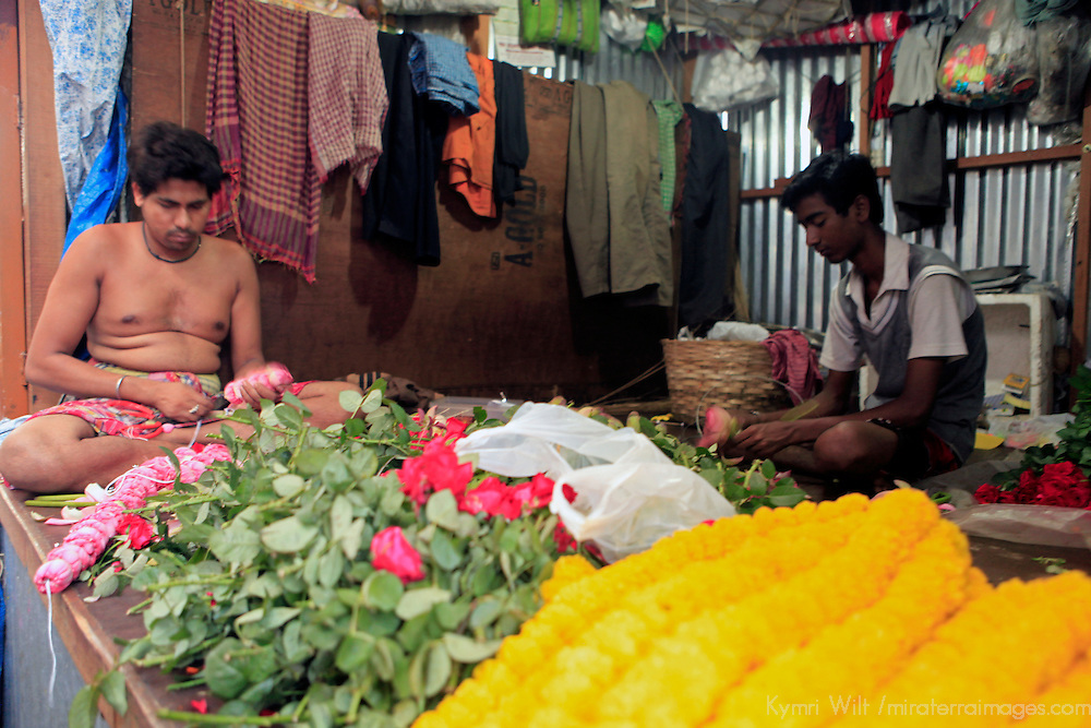 Asia, India, Calcutta. Scene from the flower market in Calcutta, where the men are stringing garlands of fresh flowers.