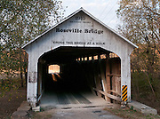 "Roseville Covered Bridge (263 feet long) was built in Burr Arch style over Big Raccoon Creek in 1910 by Van Fossen in Parke County, Indiana, The traditional ""Cross this bridge at a walk"" sign requires slow vehicle speed. The ""light at the end of the tunnel"" beckons."