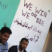 Two local residents stand near a pro-revolution graffiti in central Zawiyah.