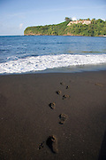footprints, Mataiva Bay, black sand beach, Island of Tahiti, French Polynesia<br />