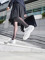 Business woman wearing running shoes walking up steps low section low angle view