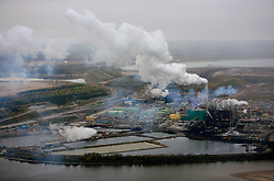CANADA ALBERTA FORT MCMURRAY 28SEP09 - Aerial view of Suncor upgrader in the Boreal forest north of Fort McMurray, northern Alberta, Canada...The tar sand deposits lie under 141,000 square kilometres of sparsely populated boreal forest and muskeg and contain about 1.7 trillion barrels of bitumen in-place, comparable in magnitude to the world's total proven reserves of conventional petroleum. ..Current projections state that production will  grow from 1.2 million barrels per day (190,000 m³/d) in 2008 to 3.3 million barrels per day (520,000 m³/d) in 2020 which would place Canada among the four or five largest oil-producing countries in the world...The industry has brought wealth and an economic boom to the region but also created an environmental disaster downstream from the Athabasca river, polluting the lakes where water and fish are contaminated. The native Indian tribes of the Mikisew, Cree, Dene and other smaller First Nations are seeing their natural habitat destroyed and are largely powerless to stop or slow down the rapid expansion of the oil sands development, Canada's number one economic driver...jre/Photo by Jiri Rezac / GREENPEACE..© Jiri Rezac 2009