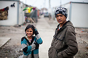 """Two young inhabitants of the Konik Refugee Camp are following the preparations for the opening of the new office of the """"Crisis Council"""" in a donated container at Konik Camp located in Podgorica, Montenegro."""