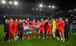 """CARDIFF, WALES - Tuesday, November 19, 2019: The Wales players celebrate with captain Gareth Bale and a supporter's flag """"Wales. Golf. Madrid"""" after the final UEFA Euro 2020 Qualifying Group E match between Wales and Hungary at the Cardiff City Stadium. Wales won 2-0 and qualifyied for the Finals. (Pic by David Rawcliffe/Propaganda)"""