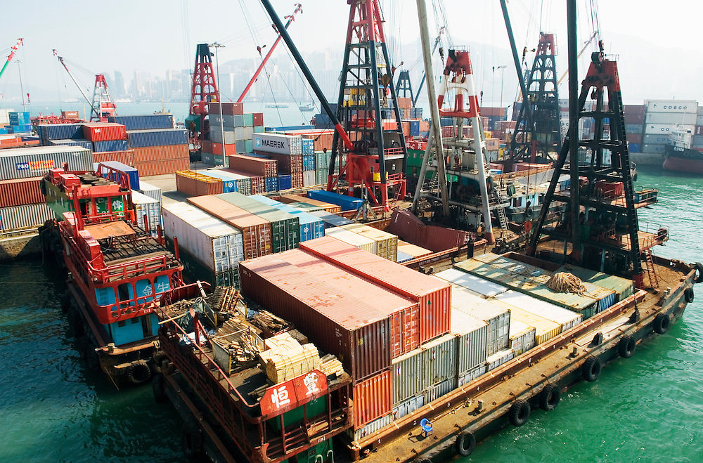 Freight container barges docked at Tsim Sha Tsui East, Kowloon with Hong Kong Island skyline across Victoria Harbour. China