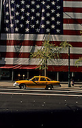 New York. Fifth avenue. giant american flag  and yellow cab.  /  drapeau americain geant et taxi jaune,