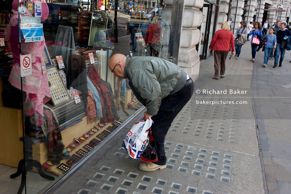 A window shopper bends down to inspect military insignia and buttons in a window on London's regent Street.