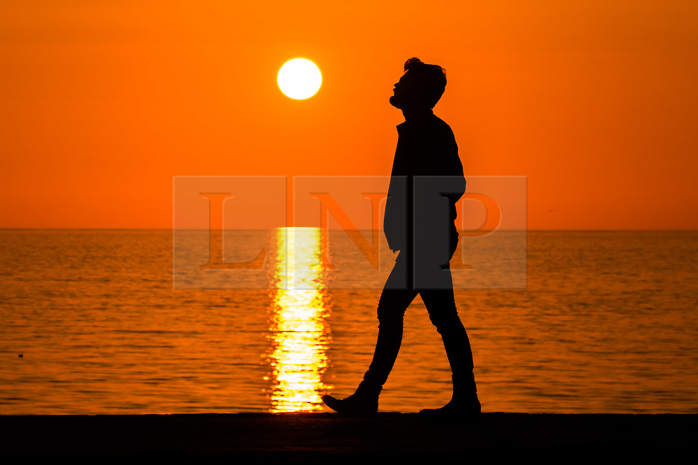 © Licensed to London News Pictures. 27/03/2019. Aberystwyth, UK. Sunset at the end of another day of warm spring sunshine on the flat calm sea at Aberystwyth, on the Cardigan Bay coast of west Wales. High pressure continues to dominate the weather for much of the UK, with settled conditions and clear almost cloudless blue skies. Photo credit: Keith Morris/LNP