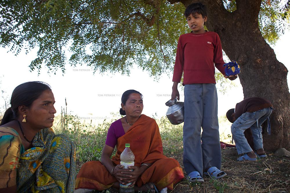 LtoR: Afsanabi, age 35; Sairabi, age 40; Shahrukh (Afsanabi's son), age 13, take a break in the shade of a tree while cutting tour dal (lentils)...Photo: Tom Pietrasik.January 2011.Maharashtra, India