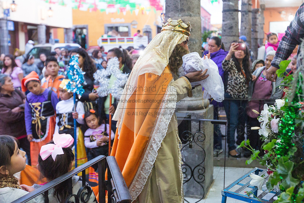 The Three Kings pick up the baby Jesus doll from a nativity crche during El Dia de Reyes January 6, 2016 in San Miguel de Allende, Mexico. The traditional festival marks the culmination of the twelve days of Christmas and commemorates the three wise men who traveled from afar, bearing gifts for the infant baby Jesus.
