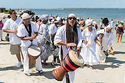 Descendants of enslaved Africans brought to Charleston in the Middle Passage hold a procession to honor their relatives lost during a remembrance ceremony at Fort Moultie National Monument June 10, 2017 in Sullivan's Island, South Carolina. The Middle Passage refers to the triangular trade in which millions of Africans were shipped to the New World as part of the Atlantic slave trade. An estimated 15% of the Africans died at sea and considerably more in the process of capturing and transporting. The total number of African deaths directly attributable to the Middle Passage voyage is estimated at up to two million African deaths.