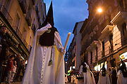 A hooded penitent in a procession during Holy week in Madrid, Spain. Street processions are organized in most Spanish towns each evening, from Palm Sunday to Easter Sunday. People carry statues of saints on floats or wooden platforms, and an atmosphere of mourning can seem quite oppressive to onlookers.