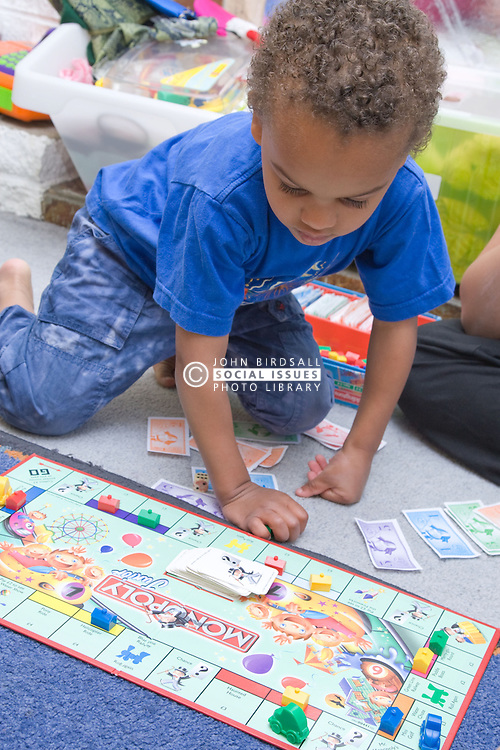 Little boy playing a game of Monopoly on the floor at home,