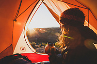 A woman enjoys the sunrise from her tent, the Wedge, San Rafael Swell, Utah.