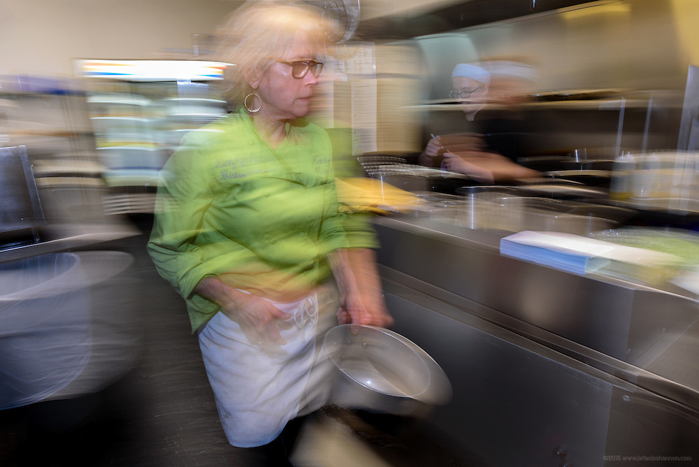 Kathy Cary, chef/owner at Lilly's Bistro and La Pesch gourmet-to-go, in motion. Lunchtime in the kitchen at Lilly's Monday, Aug. 15, 2016 with Chef/Owner Kathy Cary and staff. (Photo by Brian Bohannon)