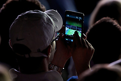 LONDON, ENGLAND - Friday, July 4, 2014: A spectator takes a photograph with his phablet (phone) during the Gentlemen's Singles Semi-Final match on day eleven of the Wimbledon Lawn Tennis Championships at the All England Lawn Tennis and Croquet Club. (Pic by David Rawcliffe/Propaganda)