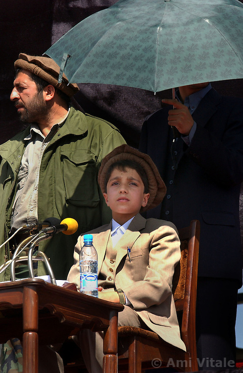KABUL,AFGHANISTAN - SEPT. 9: An Afghan holds an umbrella over the head Ahmad Massoud, the son of the slain leader Ahmad Shah Massoud during a ceremony in Kabul Sports Stadium September 9, 2002  to commemorate  the one-year anniversary of the death of his father.   (Photo by Ami Vitale/Getty Images)