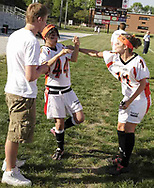 Derik Lowesch watches as Cady Holbrook (11) shoves Anita Kermani (44) to give her an idea of what to expect on the field during the 3rd Annual Powderpuff Challenge, the junior girls (class of 2008) against the senior girls (class of 2007.)