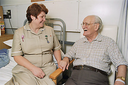 Nursing auxiliary sharing a joke with elderly patient on medical ward,