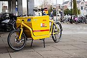 In Utrecht staat voor de ingang van winkelcentrum Hoog Catherijne een bakfiets van DHL.<br /> <br /> In Utrecht a DHL cargo bike is parked at the entrance of shopping center Hoog Catherijne.