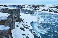 Dettifoss waterfall in North Iceland. Man standing on the edge overlooking the falls. Winter mood.