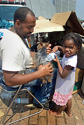 2nd Sept, 2005. New Orleans, Louisiana.<br /> Day 2 of the mass exodus. Charles Porter holds Bitty as Mijae Walker (3yrs) cools her down with water in the heat of the mid day sun outside the hellish Superdome in New Orleans as they await evacuation.Photo Credit; Charlie Varley/varleypix.com