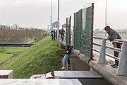 FRANCE, Calais: 17 December 2015 A refugee jumps from a bridge onto the top of a lorry in the hope of making it to England outside of the Euro Tunnel entrance in Calais this afternoon. Hundreds of refugees walked hours through Calais today to reach the Euro Tunnel from 'The Jungle' camp to try and get to England. Rick Findler  / Story