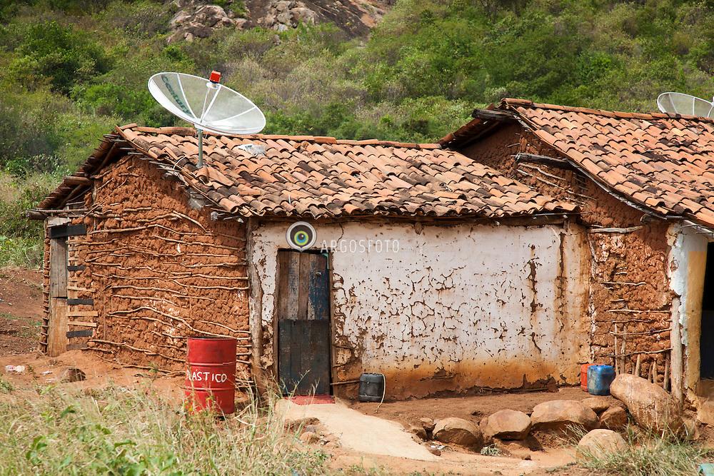 Casa de taipa com antena parabolica, no sertao pernambucano. Descarte de lixo em torno da residencia. / Rammed Earth In Serra Talhada, Brazil