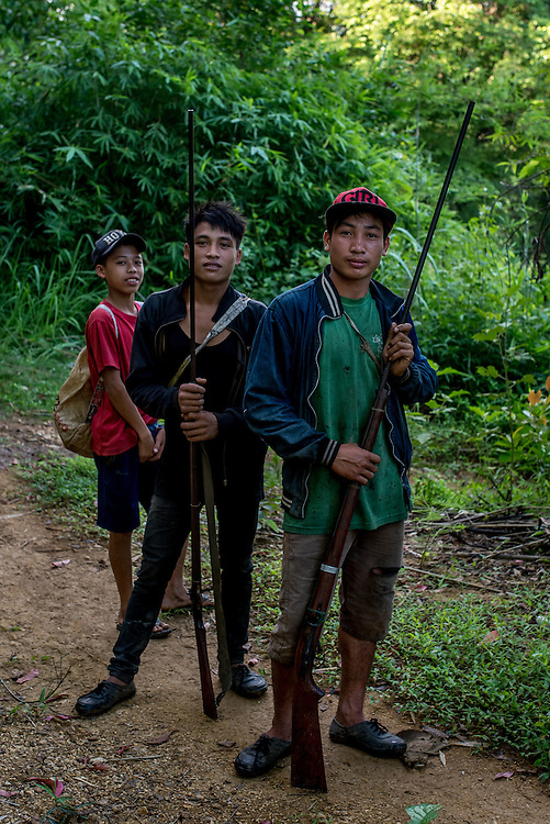 Young men outside village of Khoc Kham, hoping to lure birds out of hiding that they can shoot them with homemade shotguns.